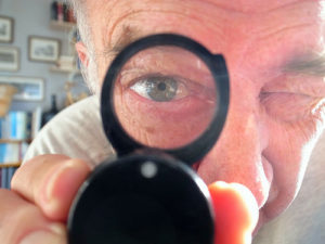 Fake Reviews? - Image of man using a magnifying glass, looking into the camera lens